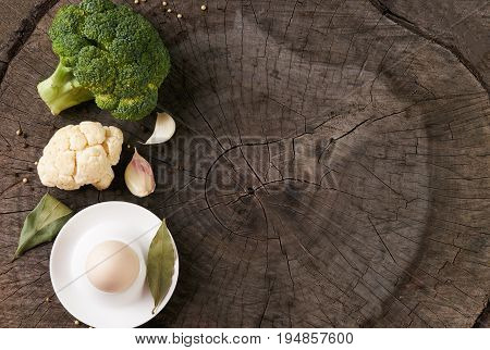 Healthy vegetables: Broccoli garlic cauliflower Chicken egg Bay leaf and seasoning on old rustic wooden background with copy space. Helathy vegetarian food and detox concept.