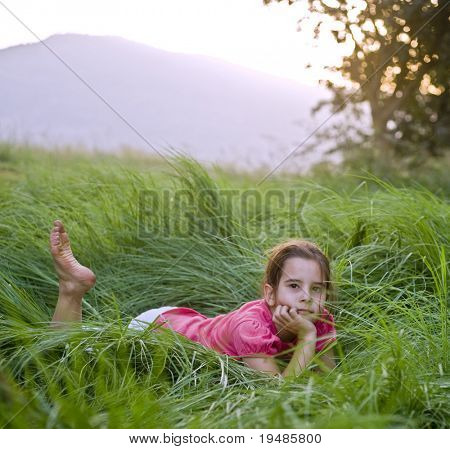 young girl lying down in the tall grass
