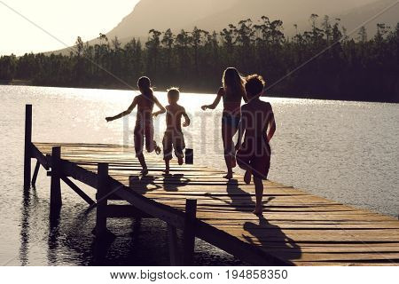 Rear view of young boys and girls running on jetty at lake