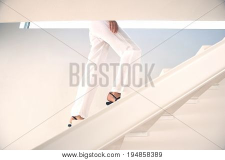 Low section of woman moving upstairs in modern home