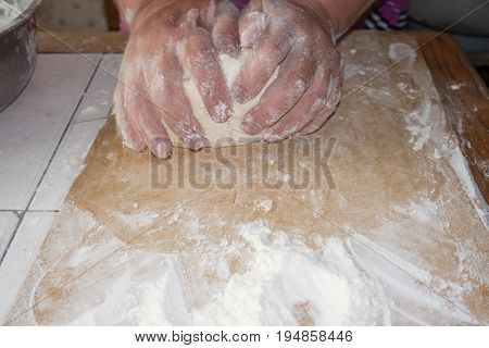 Top view shot of female hands mixing dough. Female hands knead dough on wooden board. 4k prores footage