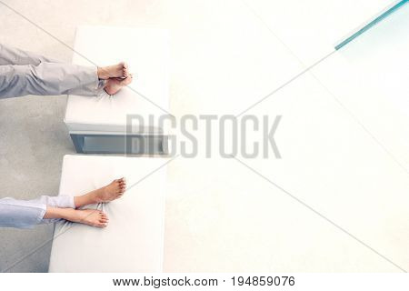 Low section of couple sitting with feet on foot stools by swimming pool