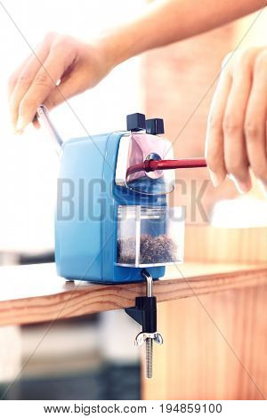 Closeup of woman's hands using manual pencil sharpener at table