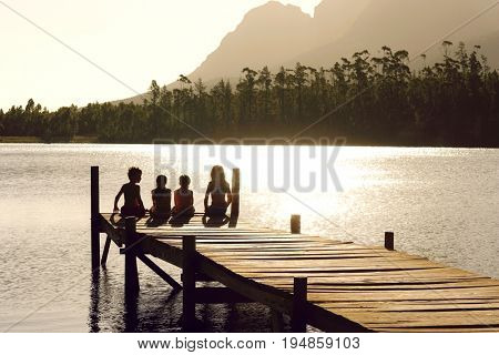 Rear view of young boys and girls sitting on edge of jetty at sunset
