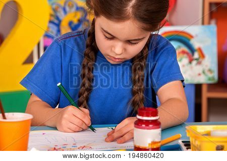 Small student girl painting in art school class. Child drawing by paints on table. Craft drawing education develops creative abilities of children. Children's ability to focus on task.