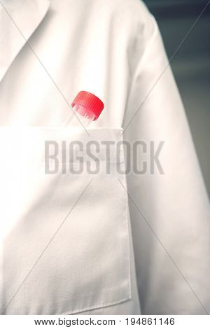 Extreme closeup of test tube in lab coat pocket