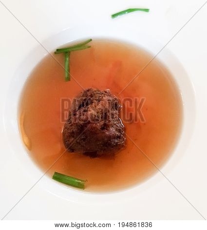 A liver dumpling soup served in abig white bowl