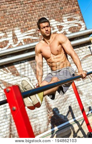 Shirtless muscular man doing workout outdoors on parallel bars.