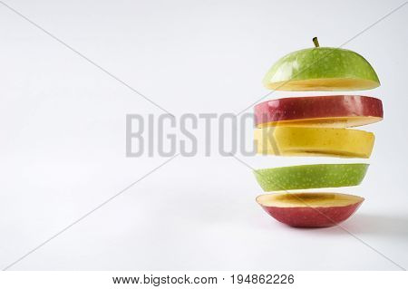 Flying colorful apples. Sliced red apple green apple and yellow apple isolated on white background with copy space. Levity fruit floating in the air. Healthy food and detox concept.
