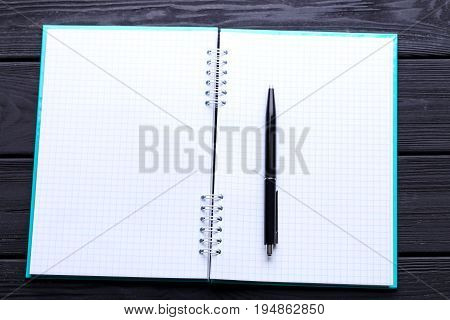 Notebook with pen on the wooden table