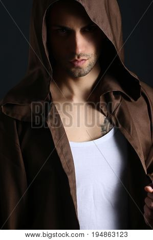 Handsome mysterious man wearing a hood on a gray background