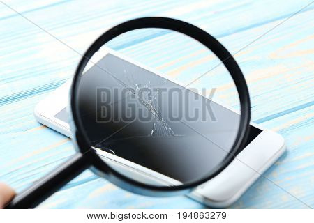 Broken smartphone in magnifying glass on a blue wooden table