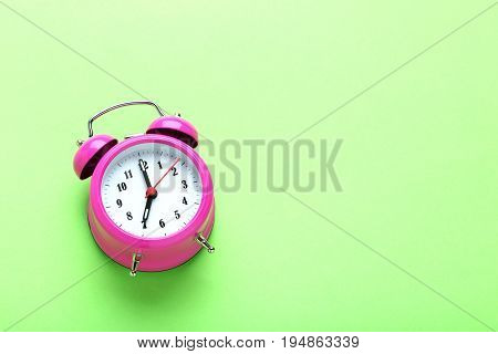 Pink alarm clock on the green background