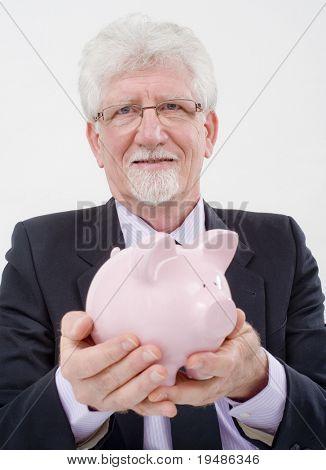 senior businessman holding  a piggy bank over white