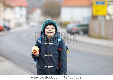 Little kid boy with eye glasses on the way to the school and eating fresh apple. Child on a street. Preschooler wearing warm clothes, glasses and backpack. Happy student or people. Education concept