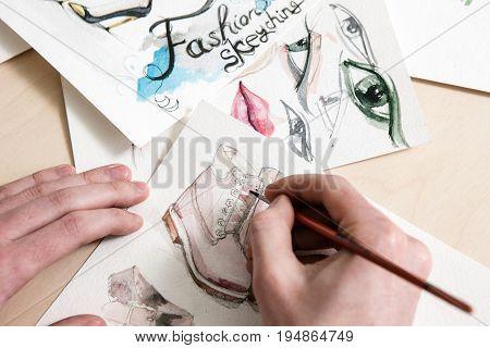 Fashion sketch in process of design. Unrecognizable man or woman draws a footwear model on desk