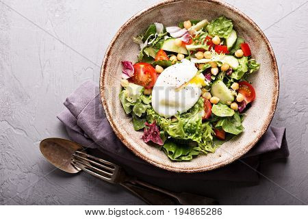Healthy and tasty salad with fresh vegetables, chickpeas and poached egg