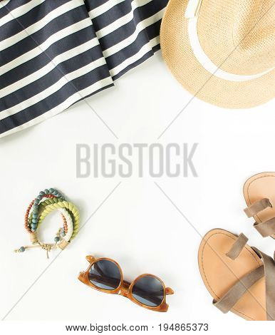 Summer fashion summer outfit on white background. Blue striped dress brown sandals retro sunglasses straw hat wod bracelet. Flat lay top view.