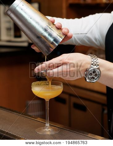 Bartender is pouring cocktail from shaker into a glass