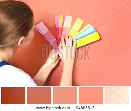 Palette with salmon color and young decorator selecting tone of wall