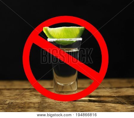 Alcohol drink in glass with STOP sign on black background