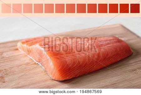 Salmon color lineal and fish fillet on wooden board