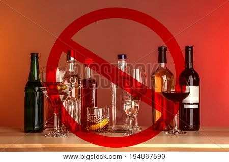 Different alcohol drinks in glassware with STOP sign on red background