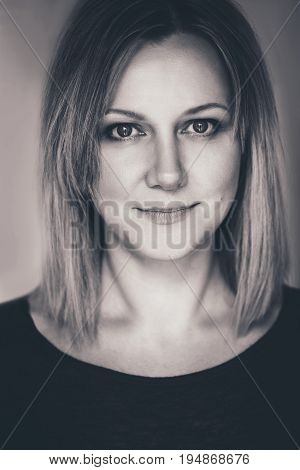 Closeup black-and-white portrait of beautiful young middle age Caucasian woman looking in camera. Woman with long blonde hair bob flirty look