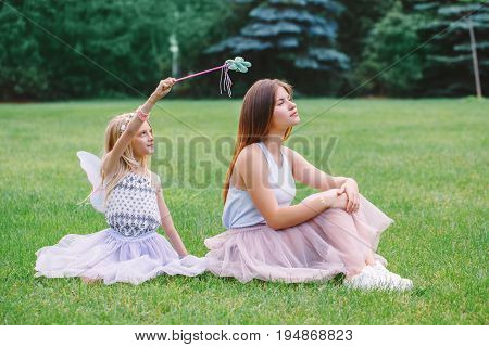 Portrait of two smiling funny Caucasian girls sisters wearing pink tutu tulle skirts in park forest meadow at sunset. Friends having fun together. Girls pretending playing fairies.