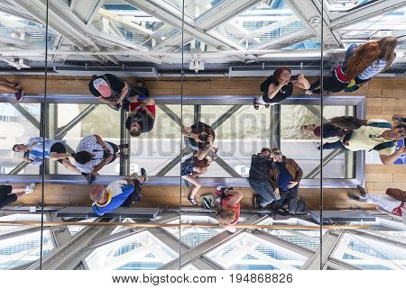 LONDON UNITED KINGDOM - JUNE 22 2017: Tower Bridge on the River Thames.Glass floor ceiling mirror tourists taking pictures. The bridge is a symbol of the city and a great attraction for tourists
