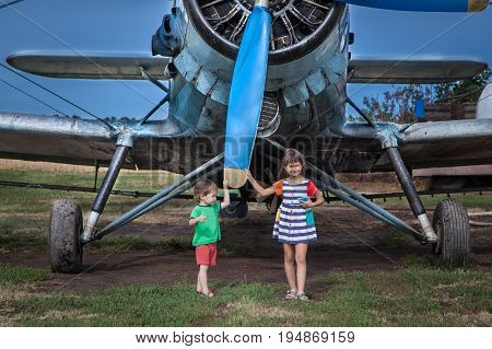 Children are staying nearby to an airplane and holding propeller	Two kids: preschool and elementary age are posing on a meadow. Agricultural biplane is behind them. Kids are holding huge propeller of the plane.