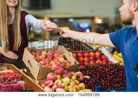 Young man paying cash at food market. Cash payment in close-up. Man pays in cash the seller of vegetables on the market.