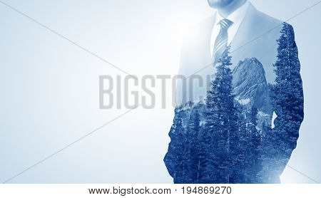 Young businessman standing and meditate with trees on the background