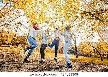 Positive happy women having fun and jumping in autumn forest
