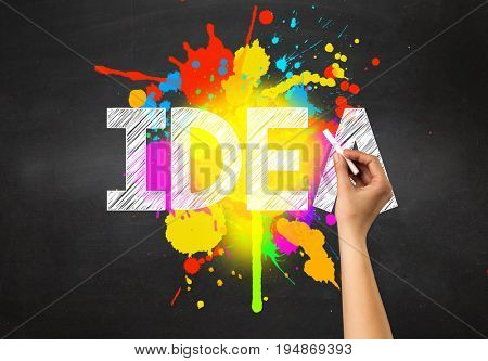 Female hand holding white chalk in front of a blackboard with idea written on it and a colorful splash in the background