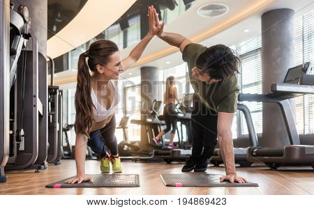 Young fit man and woman smiling and looking at camera while giving high five from basic plank pose during workout at the gym