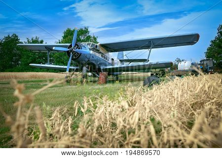 Mechanic is fixing airplane on a meadow nearby to wheat field	Old biplane has broken during watering of sunflowers fields. Mid adult man is trying to fix it.