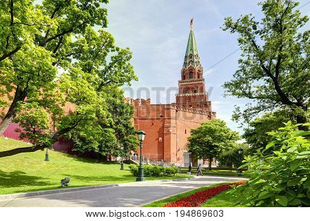 View on Moscow Red Square Kremlin tower Borovitskaya bashnya, Kremlin red brick wall, green trees and flowers of Alexander Garden (Aleksandrovskiy Sad). Famous sightseeing of Moscow Kremlin Red Square