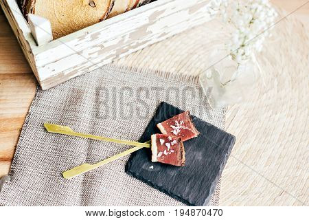 Tasty cured meat thin sliced and seasoned with sea salt and extra virgin olive oil on sticks as little tapas to snack on during wedding or party