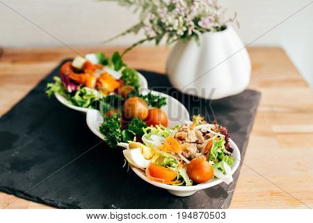 Delicious fresh vegan raw paleo vegetarian salad with cherry tomatoes shredded cabbage and carrot served on chalk board