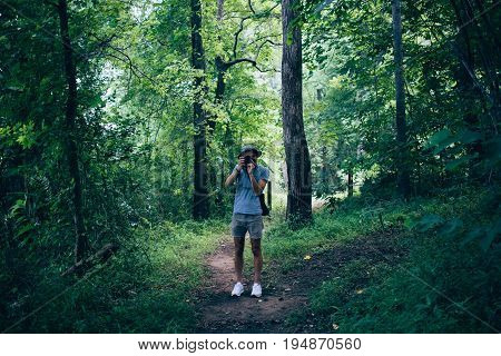 Young nomad millennial hipster photographer makes photos inside national park american forest wears panama hat and short shorts concept adventure and summer vibes