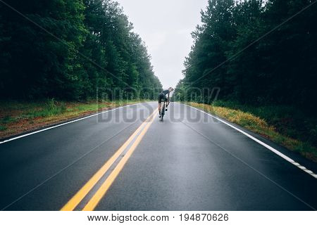 Selective focus shot of professional road cyclist riding down wet and windy mountain road in forest on aero road bike from carbon