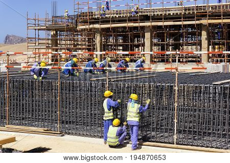 DUBAI, UAE - MAY 10, 2016: Construction workers preparing rebars for concrete foundation in Dubai, UAE on May 10, 2016