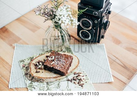 Tasty delicious sugar desert brownie crispy warm cake with sugar powder and dark chocolate flakes on top decorated on serving plate