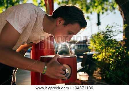 Cute handsome american young hipster teenager man in white tshirt drinks water from street fountain with beautiful shadow sun light leaks beaming on drops healthy hydration