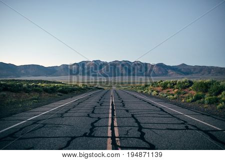 Analog film effect vintage photo of cracked old tarmac road highway in middle of nowhere in northern california smoky mountains in horizon concept adventure freedom