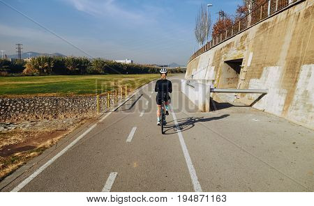 Young professional athlete woman on road carbon aero bicycle rides empty bike lane in middle of city protected by helmet