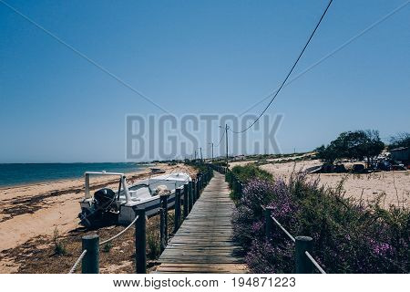 Wooden deck and walk goes into distance on empty beach with abandoned old fishing motorboats and little huts hot summer day unconventional travel destination for nomads