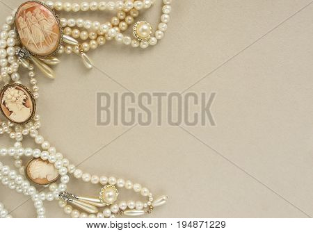 Woman's Jewellery. Frame with old vintage brooches cameos pearl beads pearl earrings. Beautiful vintage jewelry on grey. Flat lay top view