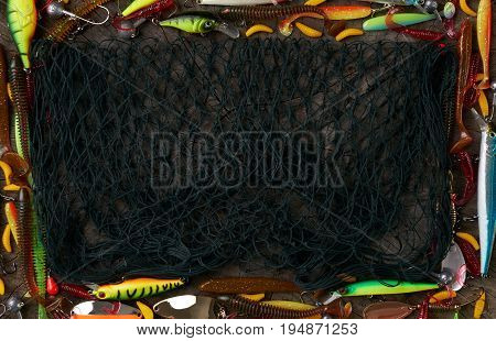 Frame of fishing tackle - fishnet fishing rod fishing line hooks and baits on a wooden background. Top view copy space.